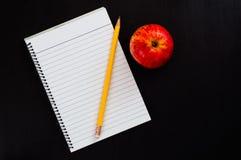 Draufsicht zur leeren gezeichneten Seite des Notizbuches mit Apple und gelbem Bleistift Stockfotos