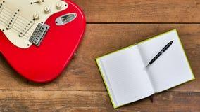Draufsichtarbeitsplatz mit leerem Notizbuch, Stift und E-Gitarre O Lizenzfreies Stockbild