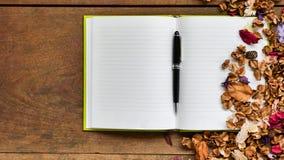Draufsichtarbeitsplatz mit leerem Notizbuch, Stift und Trockenblumen an Lizenzfreie Stockfotografie