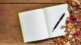 Draufsichtarbeitsplatz mit leerem Notizbuch, Stift und Trockenblumen an Stockfotos