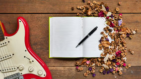 Draufsichtarbeitsplatz mit Notizbuch, Stift, E-Gitarre und getrocknet Lizenzfreies Stockfoto