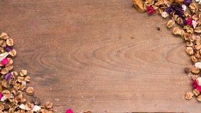Draufsichtarbeitsplatz mit Trockenblumen auf Holztischhintergrund Stockbilder