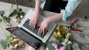 Draufsichtbürotischschreibtisch Arbeitsplatz mit, Laptop, poene Rosen blüht Blumenstrauß, Floristenarbeitsplatz mit nitebook, Fra stock video footage