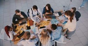 Draufsichtberufsteilhabergruppe, die zusammen an vermarktenden Dokumenten im modernen Büro hinter Tabelle arbeitet stock footage