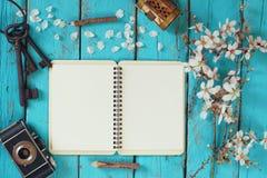 Draufsichtbild Blütenbaums des Frühlinges des weißen Kirsch, offenes leeres Notizbuch, alte Kamera auf blauem Holztisch Stockfotografie