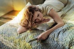 Draufsichtbild der traurigen Frau dieses Lügen auf ihrem Bett Lizenzfreies Stockfoto