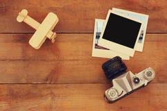 Draufsichtbild des alten leeren sofortigen Fotos, des hölzernen Flugzeugs und der alten Kamera über Holztisch Stockbild