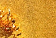 Draufsichtbild des gelockten goldenen Bandes über strukturiertem Funkelnhintergrund Stockbilder