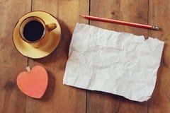 Draufsichtbild des leeren zerknitterten Papiers, Kaffeetasse und Herz formen über Holztisch Stockfotografie
