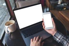 Draufsichtbild des Modells der Geschäftsfrau weißen Handy mit leerem Bildschirm mit Laptop und Kaffeetasse auf Holztisch halten stockfoto