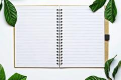 Draufsichtbild des offenen Notizbuches mit Leerseiten auf weißem Schreibtisch, der wurde durch Blätter eines Weinleseart-Grüns um Stockbild