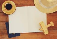 Draufsichtbild des offenen Notizbuches mit Leerseiten, Tasse Kaffee-Weidenhut und hölzernem Flugzeug über Holztisch bereiten Sie  Lizenzfreies Stockfoto