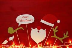 Draufsichtbild des Weihnachtskonzeptes Weihnachtsmann-Bart und -hut auf rotem hölzernem Hintergrund Stockfoto