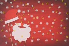 Draufsichtbild des Weihnachtskonzeptes Weihnachtsmann-Bart und -hut auf rotem hölzernem Hintergrund Stockfotos