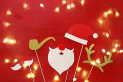 Draufsichtbild des Weihnachtskonzeptes Weihnachtsmann-Bart und -hut auf rotem hölzernem Hintergrund Stockfotografie