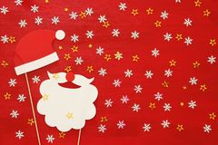 Draufsichtbild des Weihnachtskonzeptes Weihnachtsmann-Bart und -hut auf rotem hölzernem Hintergrund Lizenzfreie Stockfotografie