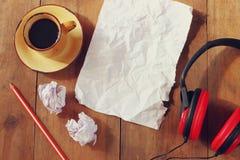 Draufsichtbild des zerknitterten Papiers nahe bei Kopfhörern und Tasse Kaffee über Holztisch Lizenzfreie Stockfotografie