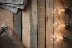 Draufsichtbild mit bulbligt Girlande und Segeltuch bauscht sich auf rohem rustikalem Hintergrund lizenzfreies stockfoto