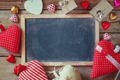 Draufsichtbild von bunten Herzformschokoladen, von Gewebeherzen, von Geschenkboxen und von Kreidebrett auf Holztisch Stockbilder