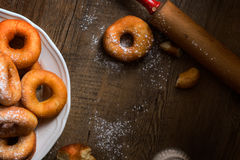 Draufsichtdetail über ein Bündel frische selbst gemachte Schaumgummiringe (Donuts) auf einer weißen Platte, mit Zuckerschüssel, N Lizenzfreies Stockbild