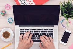 Draufsichtebene legen Arbeitsplatzmodell mit Smartphone und öffnen Laptop mit bemannt Hände auf Schreibtisch lizenzfreie stockbilder
