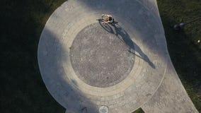 Draufsichtfahrradfrau, die ein Fahrrad auf runde Straße im Stadtpark reitet stockfotografie