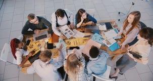 Draufsichtgruppe Geschäftsleute arbeiten im hellen modernen Büro, der junge weibliche Führer zusammen, der mit behilflicher Fr stock footage