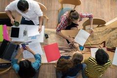 Draufsichtgruppe Jugendfreunde, zum bemüht zu sein, im Team mit Berichten und im Laptop an der Universität zu arbeiten lizenzfreie stockfotos