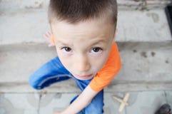 Draufsichtjungenporträtnahaufnahme, die auf Treppe sitzt Kindergesicht Kaukasisches Kind Fisheye-Effekt Fisch-äugiger Schuss stockfotografie