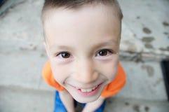 Draufsichtjungenporträtnahaufnahme Lächelndes Kindergesicht Kaukasisches Kind Fisheye-Effekt Fisch-äugiger Schuss stockbild