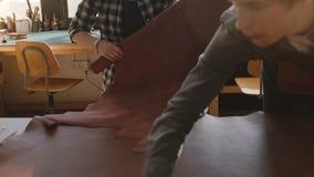 Draufsichtlebensstil geschossen vom Mann und von Frau, die in einer Herstellungswerkstatt mit Stücken Leder auf einer Tabelle zus stock video
