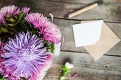 Draufsichtmehrfarbenaster blüht Blumenstrauß, Stift, weiße Grußkarte des freien Raumes und Kraftpapierumschlag auf rustikalem Hol stockbild
