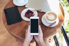 Draufsichtmodellbild von den Händen, die weißen Smartphone mit leerem Bildschirm, Tablette, Laptop, Kaffeetasse und Kuchen auf Ho stockfoto