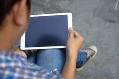 Draufsichtmodellbild von den Mannhänden, die weißen digitalen Tabletten-PC mit schwarzem leerem Tischplattenschirm in Handwann ha stockfoto