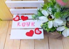 Draufsichtnahaufnahme Liebestext auf dem Holzweiß mit Herzen und Unschärfe blühen, Valentinsgruß ` s Tag Lizenzfreie Stockfotografie