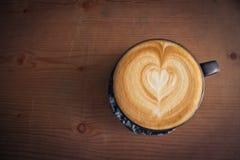 Draufsichtoberflächenherzform des Tasse Kaffees im hölzernen Hintergrund Lizenzfreie Stockbilder
