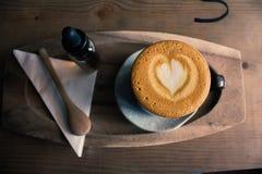 Draufsichtoberflächenherzform des Tasse Kaffees im hölzernen Hintergrund Lizenzfreies Stockfoto
