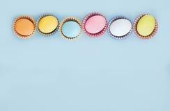 Draufsichtpastellfarben ärgert Reihe auf einem blauen Hintergrund Lizenzfreie Stockbilder