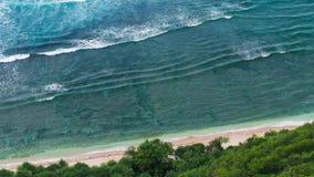 Draufsichtperspektive von den Wellen, die eins nach dem anderen zum Nunggalan-Strand, Uluwatu, Bali, Indonesien rollen stock video