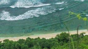 Draufsichtperspektive von den Wellen, die eins nach dem anderen zum Nunggalan-Strand, Uluwatu, Bali, Indonesien rollen stock video footage