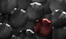 Draufsichtregenschirme Rot in der Masse des Schwarzen Stehen Sie heraus von der Kundenberaterin Stockfotos