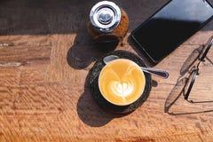 Draufsichtschale heißer Milchkaffee mit Lattekunst, Smartphone, Augengläsern und braunem Zucker auf dem hölzernen Schreibtisch mo stockbilder