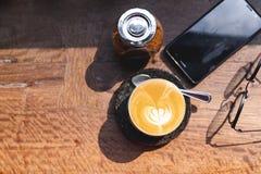 Draufsichtschale heißer Milchkaffee mit Lattekunst, Smartphone, Augengläsern und braunem Zucker auf dem hölzernen Schreibtisch mo lizenzfreies stockbild