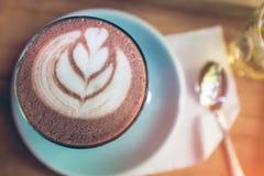 Draufsichtschale Kunst der heißen Schokolade auf Untertasse mit Löffel und Tee Lizenzfreie Stockfotografie
