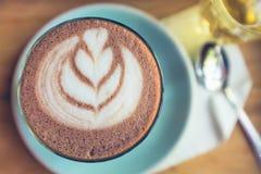 Draufsichtschale Kunst der heißen Schokolade auf Untertasse mit Löffel und Tee Stockbild