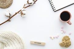 Draufsichtschreibtisch Arbeitsplatz mit Baumwollblumen-, -notizbuch-, -eibisch- und -hafermehlplätzchen Herbst- oder Winterkonzep lizenzfreie stockfotografie
