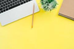 Draufsichtschreibtisch mit Laptop, Notizbücher und Anlage kopieren Raum auf Farbhintergrund stockfotos