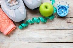 Draufsichtschuh, messendes Band, grüner Apfel, Wecker und Tuch auf hölzernem Tabellenhintergrund lizenzfreie stockfotografie