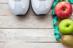 Draufsichtschuh, messendes Band und Apfel auf hölzernem Tabellenhintergrund lizenzfreie stockfotografie