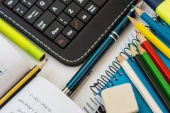 Draufsichtschulbedarf, Laptoptablettentastatur, mehrfarbige Bleistifte, Leuchtmarker, Gummi, Stift, öffnete Mathematikarbeitsbuch Stockfoto